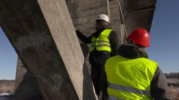 Workers talking under the bridge