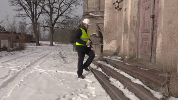 Mérnök kávét iszik, régi épület közelében