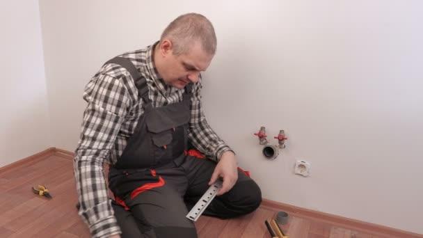 Klempner arbeitet in der Nähe von Hähnen