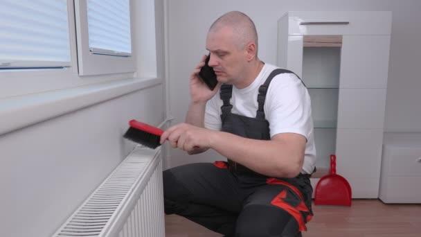 Klempner putzt Heizkörper und telefoniert
