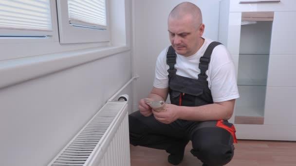 Muž počítání peněz u radiátoru