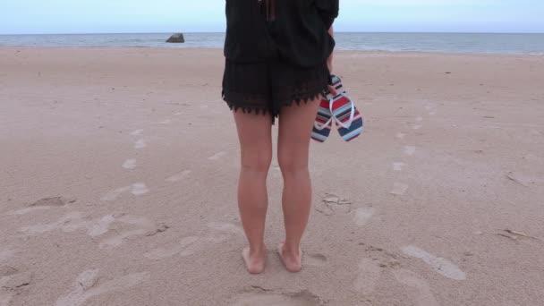 Nő a flip papucs a tenger közelében