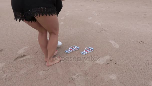 Woman with flip flops on the beach
