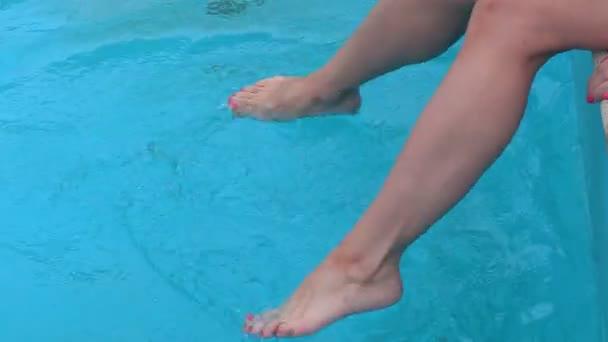 Žena s bosýma nohama šplouchání vody v bazénu
