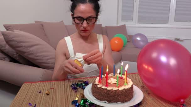 Nő közelében születésnapi torta fél égő gyertyát