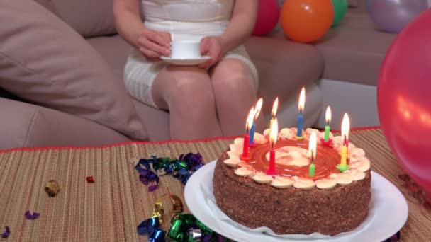 Frau mit Tasse Kaffee sitzt auf Sofa neben Geburtstagstorte mit brennenden Kerzen