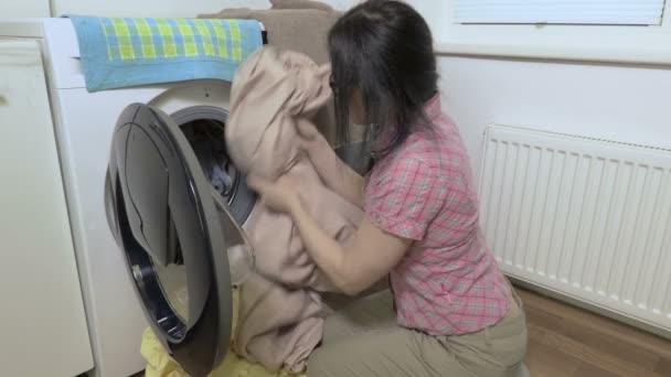 Žena s prádlo na podlahu u pračky