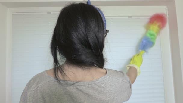 Úklid pokoje žena poblíž okna