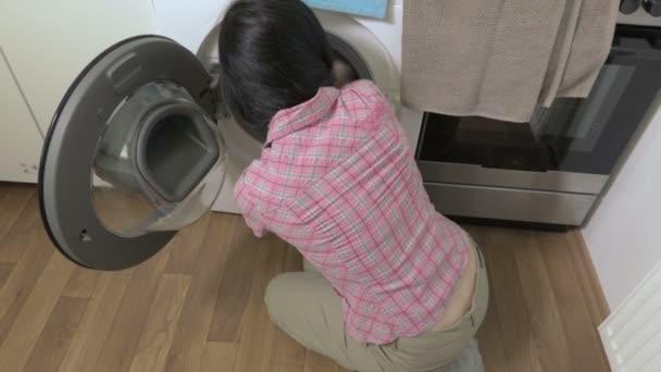 Frau steckte Wäsche in Waschmaschine