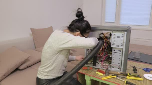 Frau benutzt Staubsauger in der Nähe eines kaputten Computers
