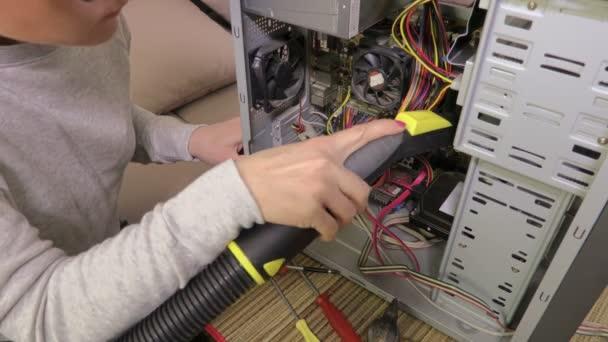 Frau säubert Computer mit Staubsauger