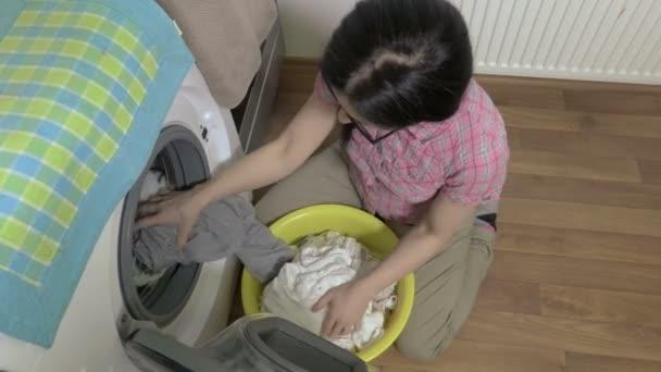 Žena vyndat prádlo z pračky