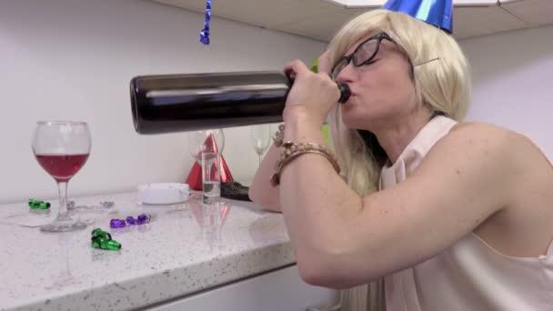Opilá žena s lahví vína u stolu