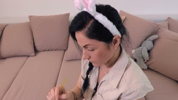 Žena zdobí velikonoční vajíčka