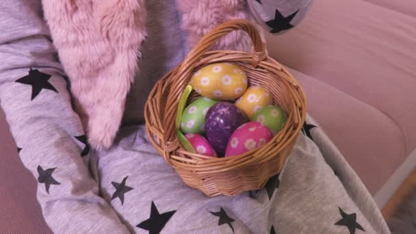 Little girl with Easter eggs in basket and carrot on sofa