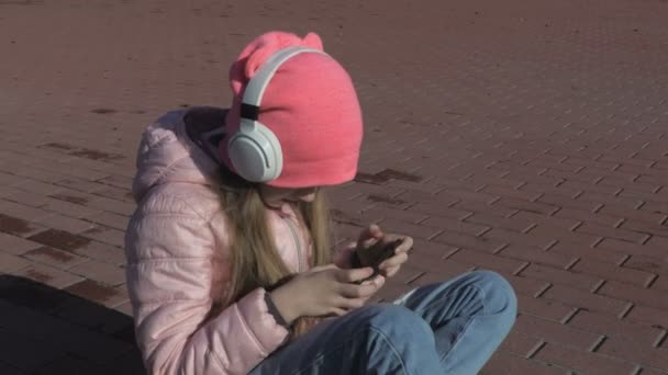 Little girl child wearing headphones and sitting on skateboard.Wireless Freedom With Bluetooth Technology concept