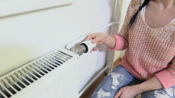Frau in Heizkörpernähe stellt Thermostat ein