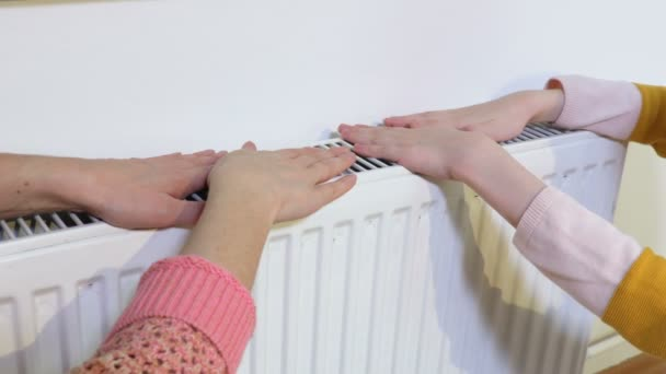 Tochter und mutter wärmen ihre hände auf radiator