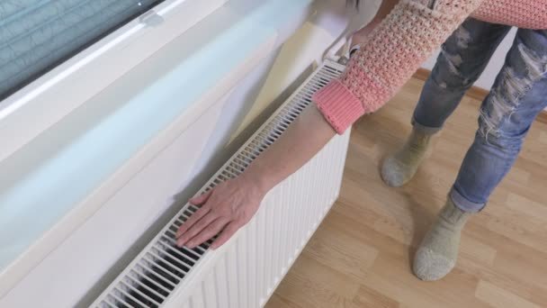 Frau streift Heizkörper im Winter