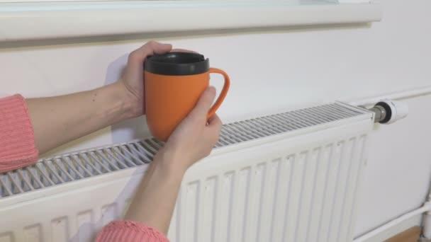 Frau hält Tasse Tee auf dem warmen Heizkörper