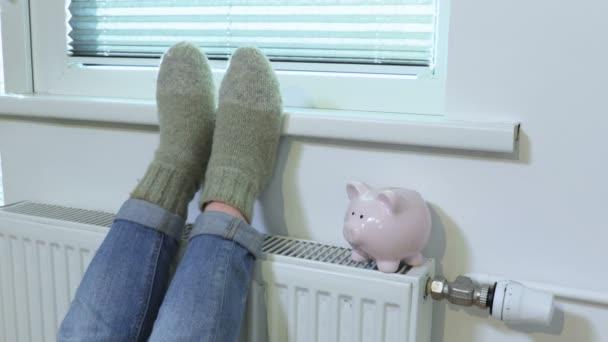 Frau wärmt sich im Winter bei Sparschwein am Heizkörper auf