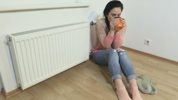 Frau trinkt Tee in der Nähe des Heizkörpers