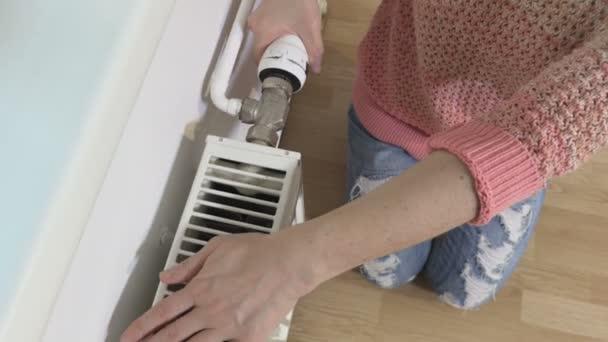Frau justiert Thermostat am Heizkörper aus nächster Nähe
