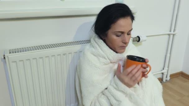 Frau mit Karo sitzt vor Heizkörper und trinkt Tee