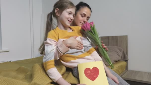 Child daughter congratulate mom and give her flowers tulips. Mum and daughter smiling and hugging