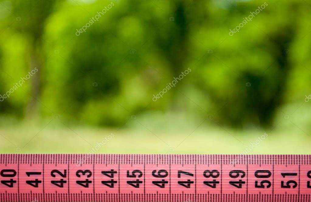 Measuring tape, lose weight, diet rear view grass bush tree blurred background sport
