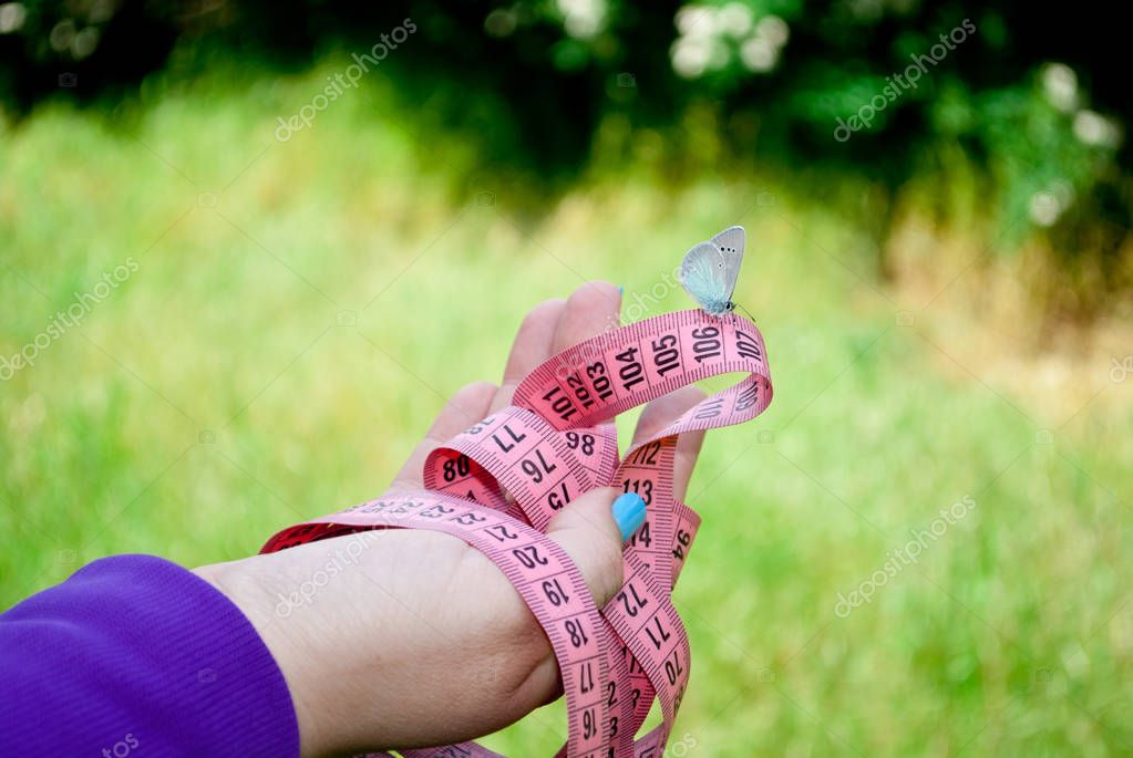 on the hand of a fat woman girl who wants to lose weight diet and holds in her hands a measuring tape of pink color figures, sits a blue white butterfly, a hand with short blue nails on a blurred background, easiness to flit, side view