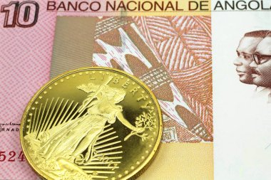 A macro image of a colorful ten kwanza bill from Angola with a gold coin.  Shot close up.