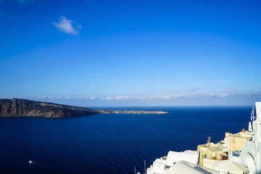 Panoramic view of vast blue Aegean sea, sailing ships and natural caldera mountain from Oia village with white buildings along island foreground and blue sky copy space background