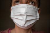 eine Frau trägt eine Gesichtsmaske aus Papier über Mund und Nase, um zu provozieren