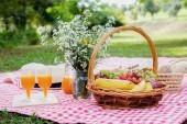Klobouk, květina a piknik proutěný koš s jídlem, chléb, ovoce a
