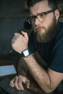bearded man in eyeglasses during work