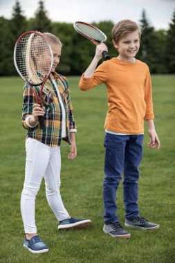 Siblings with badminton racquets