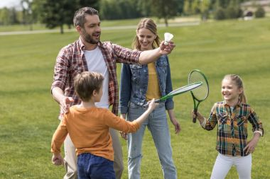 happy family playing badminton in park