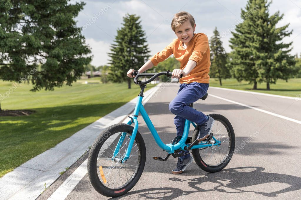 smiling kid boy riding bicycle