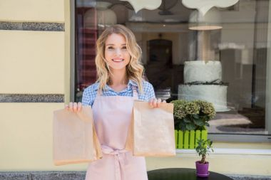 Waitress holding paper bags