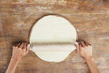 Hands rolling dough