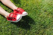 Dítě v teniskách na trávě