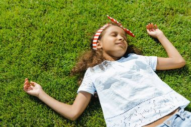 African american girl sleeping on grass
