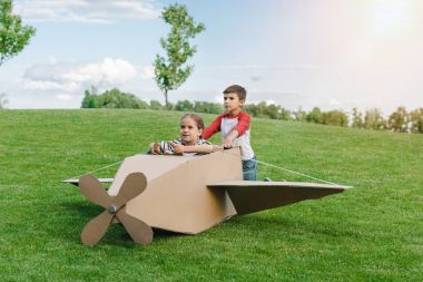 Children playing with plane in park