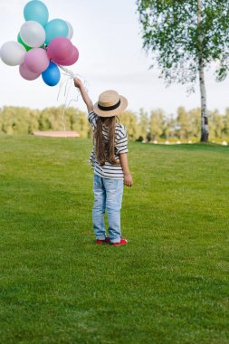 Girl with colorful balloons in park