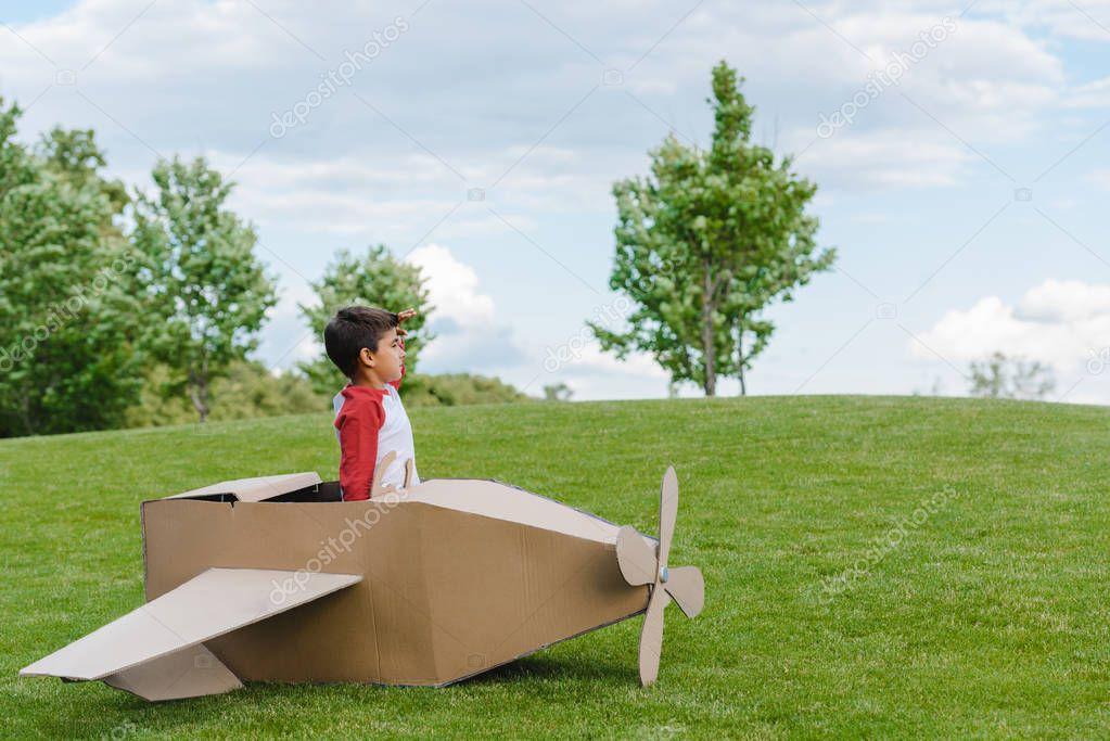Boy sitting in cardboard plane