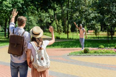 couple waving to friend