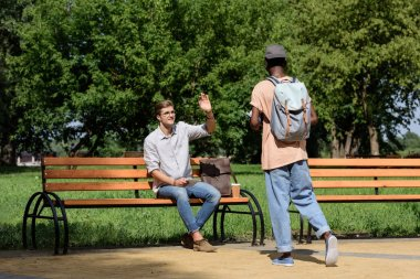 man waving to friend in park