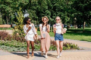 multicultural women walking in park
