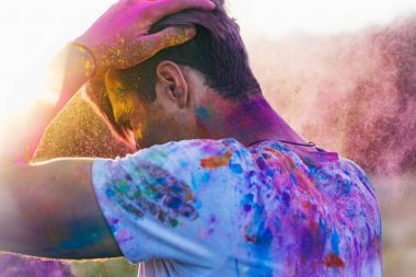 Side view of caucasian man with powder on clothing during holi festival stock vector